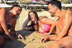 Personnes heureuses détendant sur la plage et la communication Photographie stock libre de droits