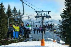 Personnes heureuses dans le télésiège sur la station de sports d'hiver Image stock