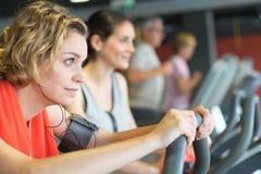 Personnes heureuses faisant faire du vélo d'intérieur dans le centre de fitness Image stock