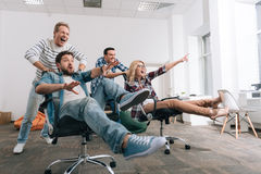 Personnes heureuses joyeuses s'asseyant dans les chaises de bureau Photos libres de droits