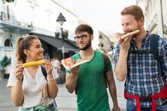 Personnes heureuses mangeant des aliments de préparation rapide dans la ville Photographie stock libre de droits