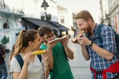 Personnes heureuses mangeant des aliments de préparation rapide dans la ville Photos libres de droits