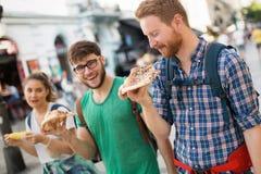 Personnes heureuses mangeant des aliments de préparation rapide dans la ville Photo stock