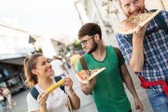 Personnes heureuses mangeant des aliments de préparation rapide dans la ville Image stock