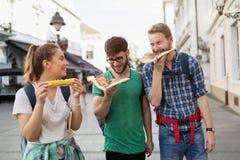 Personnes heureuses mangeant des aliments de préparation rapide dans la ville Photos stock