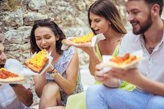 Personnes heureuses mangeant des aliments de préparation rapide dans la ville tout en voyageant Photographie stock