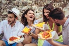Personnes heureuses mangeant des aliments de préparation rapide dans la ville tout en voyageant Image libre de droits