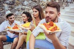 Personnes heureuses mangeant des aliments de préparation rapide dans la ville tout en voyageant Photos libres de droits