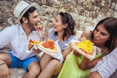 Personnes heureuses mangeant des aliments de préparation rapide dans la ville tout en voyageant Images stock
