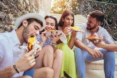 Personnes heureuses mangeant des aliments de préparation rapide dans la ville tout en voyageant Image stock