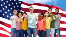 Personnes heureuses montrant des pouces au-dessus de drapeau américain Image stock