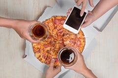 Personnes heureuses s'asseyant autour de la table mangeant le déjeuner à coworking Photographie stock libre de droits