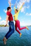 Personnes heureuses sautant par-dessus l'eau image libre de droits