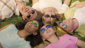 Personnes heureuses se situant en cercle sur l'herbe en parc et chansons de chant, ayant l'amusement banque de vidéos