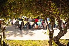 Personnes heureuses se tenant et faisant des emplettes sur une rue tranquille de fête par des branches d'arbre Images stock