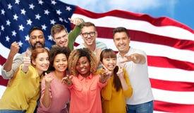 Personnes internationales faisant des gestes au-dessus du drapeau américain Images libres de droits