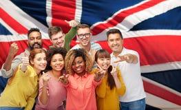Personnes internationales faisant des gestes au-dessus du drapeau britannique Image libre de droits