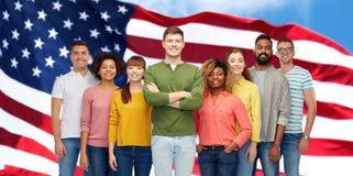 Personnes internationales heureuses au-dessus de drapeau américain Photographie stock libre de droits