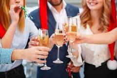Personnes joyeuses en gros plan encourageant avec des boissons une nouvelle année sur un fond brouillé Concept de vacances de Noë Image stock
