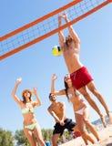 Personnes joyeuses jouant le volleyball sur la plage Photographie stock libre de droits