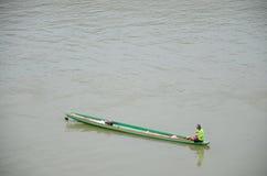 Personnes laotiennes pêchant des poissons sur le bateau en bois chez le Mekong Photos stock