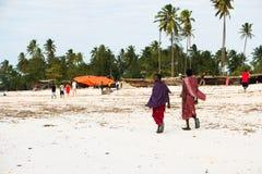 Personnes locales dans la marche le long de la plage, Zanzibar, Tanzanie Photo libre de droits