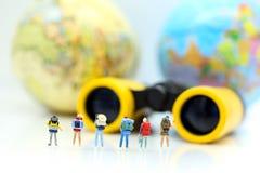 Personnes miniatures : Équipe de voyageur avec les jumelles et la carte b du monde Photo stock
