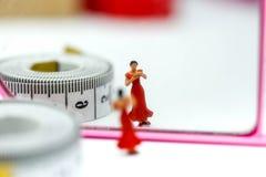 Personnes miniatures : amincissez la belle femme avec le miroir et attachez- du ruban adhésifmoi Photographie stock libre de droits