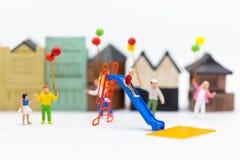 Personnes miniatures : amusement du jeu d'enfants dans le terrain de jeu Utilisation d'image pour le jour du ` s d'enfants Photographie stock