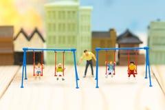 Personnes miniatures : berceau d'oscillation de père avec des enfants Utilisation d'image Photo stock