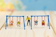 Personnes miniatures : berceau d'oscillation de père avec des enfants Utilisation d'image Photos libres de droits
