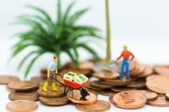 Personnes miniatures : Chariots végétaux d'utilisation d'hommes et marche sur des pièces de monnaie Utilisation d'image pour le c Images libres de droits