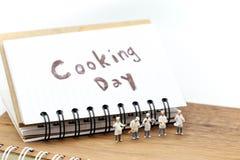 Personnes miniatures : chef faisant cuire employant pour le concept de faire cuire le jour photos stock