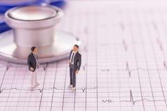 Personnes miniatures : Chiffres d'homme d'affaires se tenant sur les cardiovas Image stock