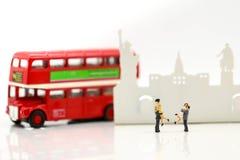 Personnes miniatures : Couples d'autobus de attente d'amour à la gare routière pour Photo libre de droits