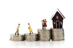 Personnes miniatures : Couples de l'amour avec la pile des pièces de monnaie et du mini h Photo libre de droits