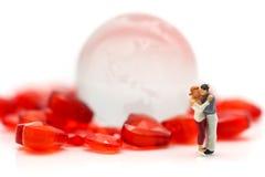 Personnes miniatures : Couples de l'amour avec le mini monde et le coeur rouge, Images libres de droits