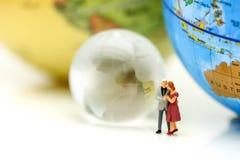 Personnes miniatures : Couples de l'amour avec le mini monde et le coeur rouge, Photo stock