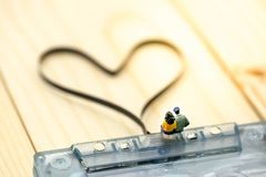 Personnes miniatures : Couples de l'amour se reposant sur la cassette sonore avec Image stock