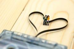 Personnes miniatures : Couples de l'amour se reposant sur la cassette sonore avec Photo libre de droits