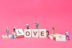 Personnes miniatures : ` D'amour de ` de mot de renforcement d'équipe de travailleur Image libre de droits