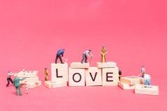 Personnes miniatures : ` D'amour de ` de mot de renforcement d'équipe de travailleur Photo stock