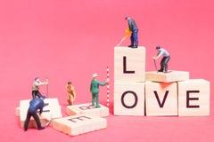 Personnes miniatures : ` D'amour de ` de mot de renforcement d'équipe de travailleur Photographie stock