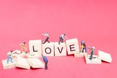 Personnes miniatures : ` D'amour de ` de mot de renforcement d'équipe de travailleur Image stock
