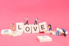 Personnes miniatures : ` D'amour de ` de mot de renforcement d'équipe de travailleur Images stock
