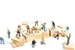 Personnes miniatures : ` D'amour de ` de mot de renforcement d'équipe de travailleur sur le bloc en bois Photos libres de droits