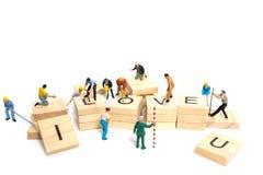 Personnes miniatures : ` D'amour de ` de mot de renforcement d'équipe de travailleur sur le bloc en bois Photographie stock libre de droits