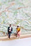 Personnes miniatures dans l'action sur une feuille de route Photos stock