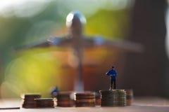 Personnes miniatures dessus sur la pile de pièce de monnaie avec l'avion de jouet de tache floue Photos libres de droits