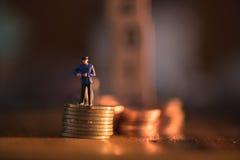 Personnes miniatures dessus sur la pile de pièce de monnaie avec l'avion de jouet de tache floue utilisant As Photos libres de droits